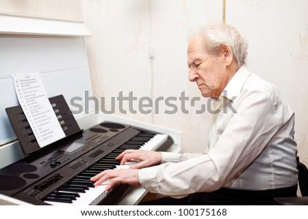 grey-haired senior man playing piano - stock photo