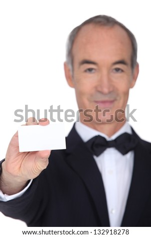 Grey haired waiter displaying business card - stock photo