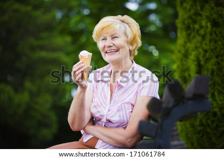 Grey-Haired Woman Relaxing with Ice-Cream on Bench in the Park - stock photo