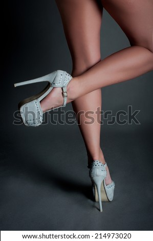 Grey high heels on beautiful female legs - stock photo