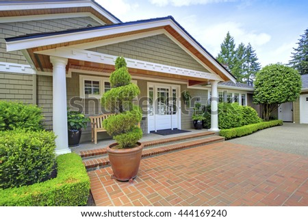 Grey house with white trim and brick walkway. View of entrance column porch. - stock photo