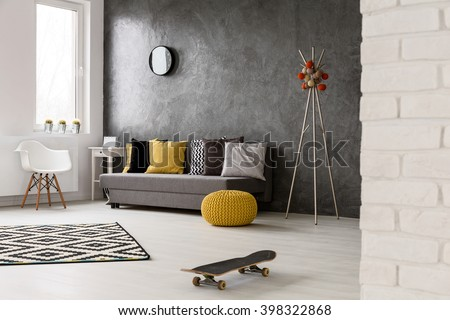 Grey interior with sofa, chair, yellow details and pattern decorations in black and white, skateboard lying on the floor  - stock photo