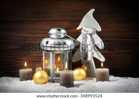 Grey lamp, fir tree, candles and baubles in a snow over wooden background, still life