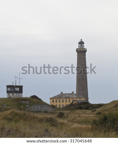 Grey Lighthouse. An unusually grey lighthouse stands beside a traditionally yellow painted northern Danish building. Sand dunes surround the lighthouse and there is a storm at sea.