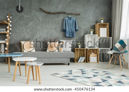 Grey living room in new style with DIY furniture, chair, pattern carpet, sofa and creative home decorations