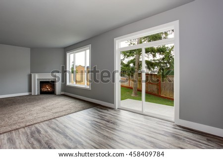 Grey living room interior with fireplace. Windows and Glass doors overlooking the back yard.