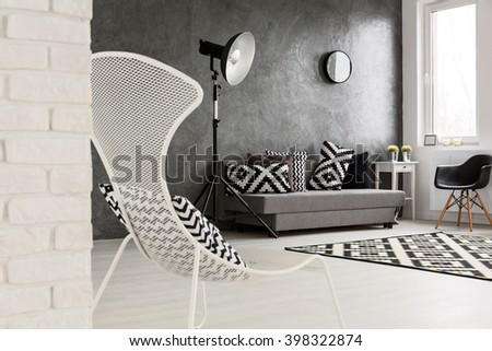Grey living room with sofa, chairs, standing lamp, brick wall and decorations in black and white