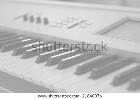 Grey-masked synthesizer, with keys and controls visible. - stock photo