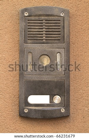 Grey metal Intercom from an apartment hanging on a beige concrete wall