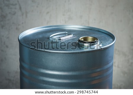 Grey metal oil and chemical drum over the white concrete wall background - stock photo