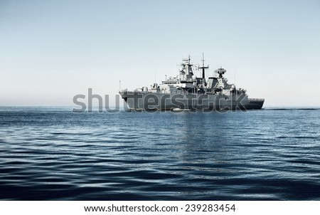 Grey modern warship sailing in still water against dramatic sky