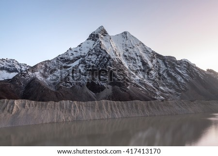 Grey moraine lake and snowy mountain peak in the morning lights in Himalayas, Nepal. Mirror water of a big moraine lake. Imja Tsho moraine lake at the foot of the Imja Glacier. - stock photo