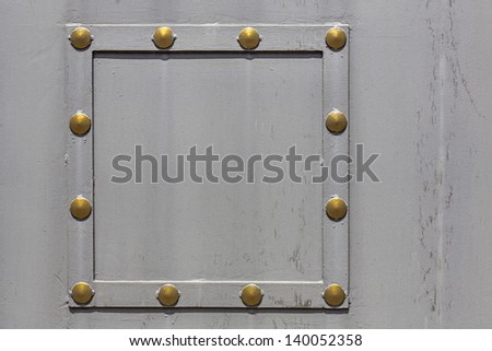 Grey painted metal plate with rivets and frame - stock photo