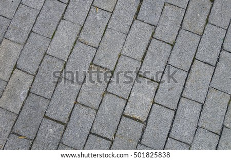 Grey pavement made of small granite tiles, background.