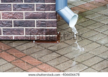 grey rain water downspout on brick wall - stock photo