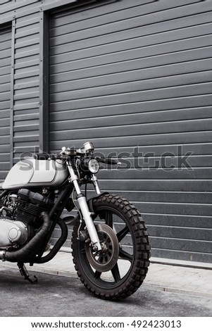 Grey rebuilt motorcycle motorbike caferacer in front of rolled gates of garage