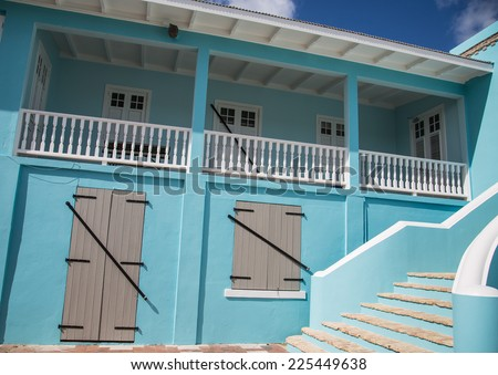 Grey shutters on blue plaster building with brick steps - stock photo