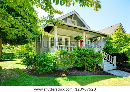 Grey small house with porch and white railings with summer landscape. - stock photo
