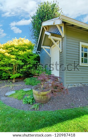 Grey small outdoor shed with backyard landscape with green summer grass.