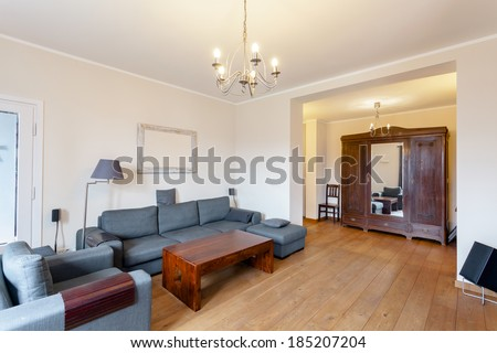 Grey sofa and armchair in spacious living room - stock photo