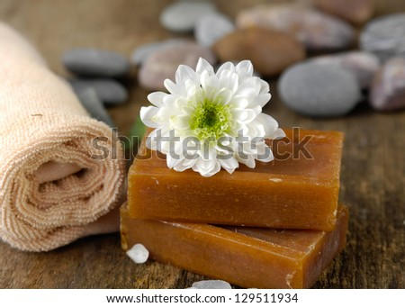 grey stones and flower with handmade soap, towel, stones on driftwood
