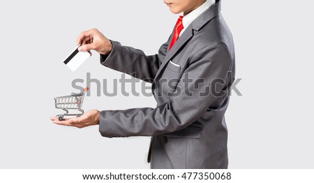 Grey suit asian business man holding credit card and small shopping cart for online shopping concept.