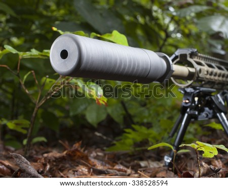 Grey suppressor on a rifle that is in a bunch of trees