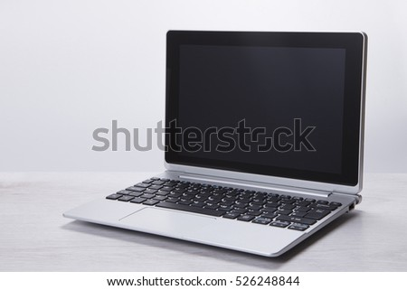 Grey toned image of an open modern laptop with a blank black screen displayed to the camera with copy space