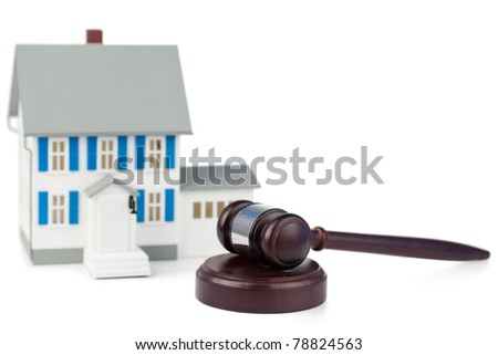 Grey toy house model and brown gavel against a white background