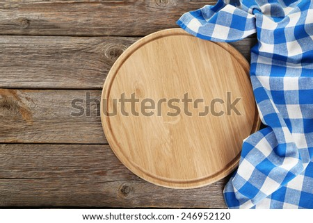 Grey wooden background with napkin with cutting board - stock photo