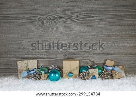 Grey wooden christmas background with turquoise decoration and gifts wrapped in paper. - stock photo