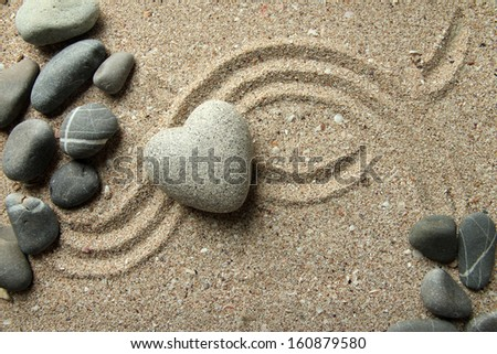 Grey zen stone in shape of heart, on sand background - stock photo
