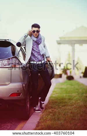 Greyhound schoolboy near the car threatens to someone from pupils - stock photo