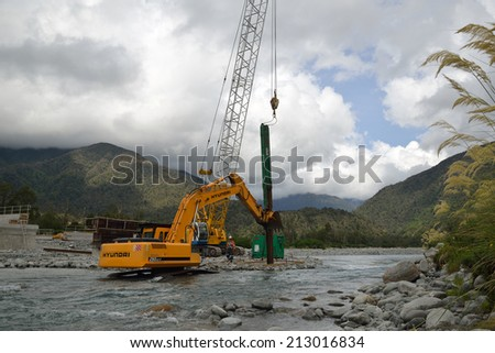 GREYMOUTH, NEW ZEALAND, CIRCA DECEMBER 2013: Builders construct a concrete bridge over a small river in Westland, New Zealand