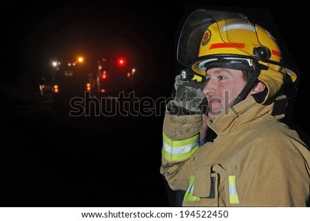 GREYMOUTH, NEW ZEALAND,  CIRCA 2006: Volunteer fire fighter uses a torch to signal men in the field during an evening bush fire near Greymouth, Westland, New Zealand