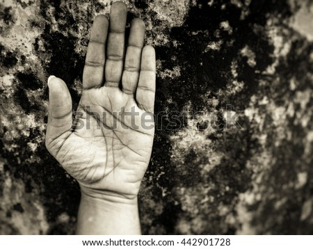 Greyscale image of hands against a dark grunge background - stock photo