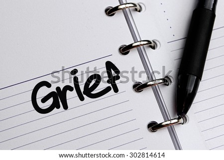 Grief word written on notebook - stock photo