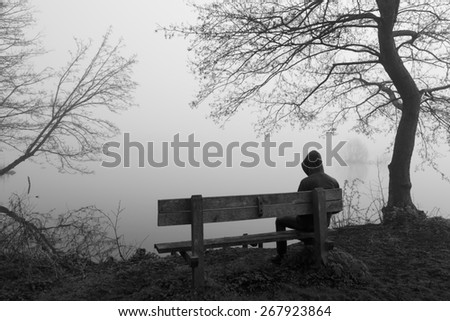 Grieving man sitting alone on a bench at a lake on a foggy day. - stock photo