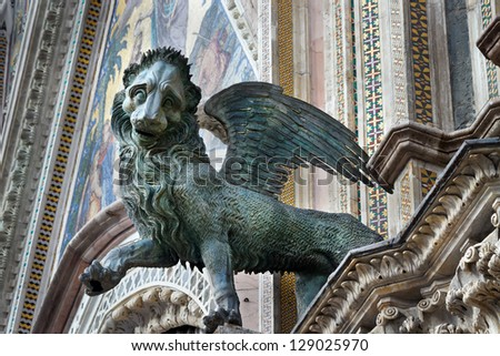 Griffin (being with a trunk of a lion and wings of an eagle) on an external facade of a Cathedral (Duomo), Orvieto, Italy - stock photo