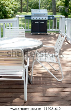 Grill and table on porch deck - stock photo
