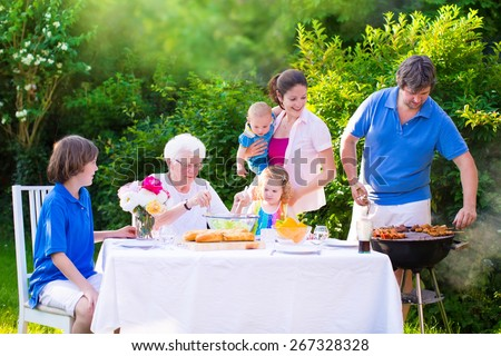 Grill barbecue backyard party. Happy big family, mother, father, age son, cute toddler daughter and baby, enjoying BBQ lunch with grandmother eating grilled meat in the garden with salad and bread.  - stock photo