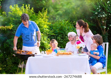 Grill barbecue backyard party. Happy big family - young mother and father with kids,  son, toddler daughter and baby, BBQ lunch with grandmother eating grilled meat in the garden with salad and bread. - stock photo