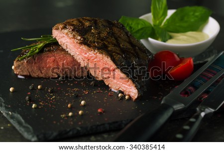 Grill beef steak on dark background with sauce and tomatoes - stock photo