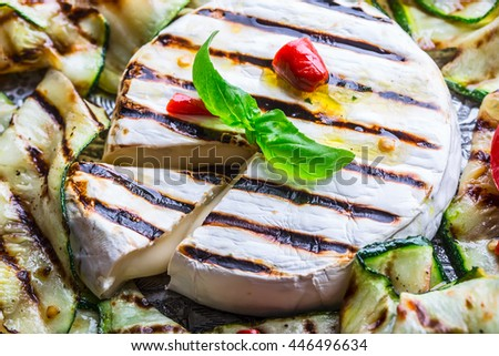 Grill Brie camembert cheese zucchini with chili pepper and olive oil. Italian mediterranean or greek cuisine. Vegan vegetarian  food.  - stock photo
