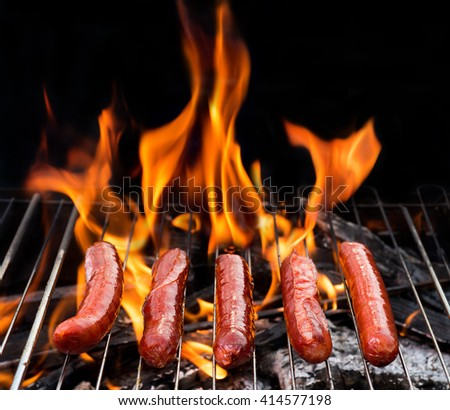 grill concept with flame. BBQ with fiery sausages on the grill - stock photo