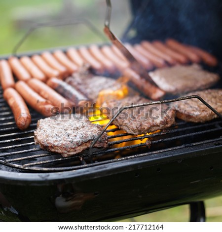 grill full of hotdogs and hamburger cooking - stock photo