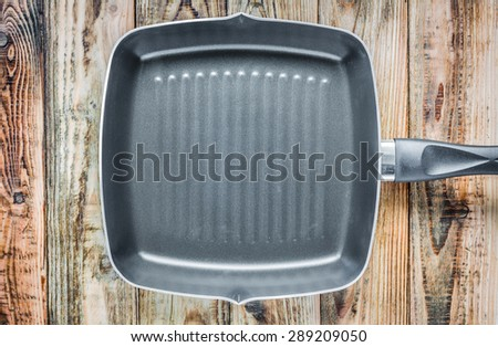 Grill pan on wood - stock photo