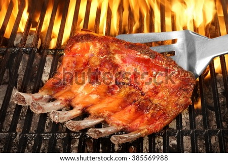 Grill Tools And BBQ Spareribs Or Baby Back Rib  On The Hot  Flaming Cast Iron Grate, Top View, Close Up