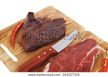 grilled and raw beef steak fillet meat with knife on wooden board isolated over white background - stock photo