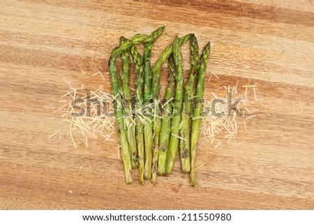 Grilled asparagus and parmesan cheese. Fresh grilled asparagus and parmesan cheese on a timber board. - stock photo
